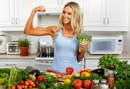 Strong woman with broccoli in the kitchen. Stock Photos