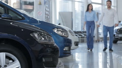 Couple walks along the row of cars at the dealership Stock Footage