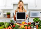 Young woman with tablet in the kitchen. Stock Photos