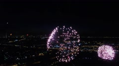 Fireworks explodes above illuminated megalopolis at dark night. Aerial view Stock Footage