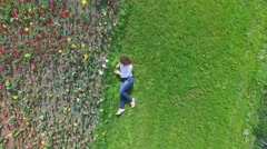 Woman lies on grass near flower field at spring sunny day Stock Footage