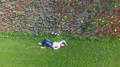 Woman lies on grassplot near flowerbed at sunny spring day. Aerial view Stock Footage