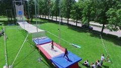 Acrobatic artists jumps on trampoline in park Luzhniki Stock Footage