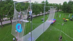 Aerialist performance on trapeze during YOTA company event in park Stock Footage
