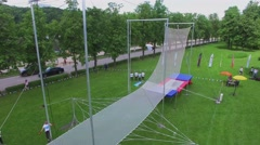 Aerial acrobats sway above net in park during YOTA company event Stock Footage