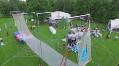 People watch aerial acrobats performance on trapeze in park Luzhniki Stock Footage