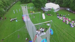 People watch aerial performance on trapeze in park Luzhniki Stock Footage
