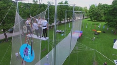 Aerialist swing above net during YOTA company event in park Stock Footage