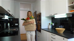 Happy young woman brings a bag of groceries to the kitchen. Stock Footage