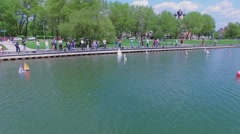 People on embankment control many toy ships which sail Stock Footage