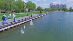 Toy ship sail by Ostankinsky pond near embankment with people Stock Footage