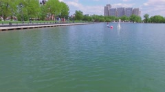 Two toy ships sail on Ostankinsky pond near quay with people Stock Footage