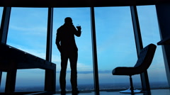 Silhouette of man drinking wine standing by window at home Stock Footage