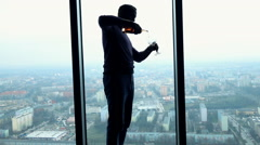 Silhouette of man pouring wine into glass by window at home, super slow motion  Stock Footage