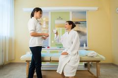 Pretty young woman wearing robe and masseuse talking after massage in a spa Kuvituskuvat