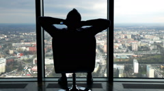 Silhouette of man relaxing on armchair and admire view form window at home Stock Footage