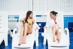 Two young women relaxing by the poolside wearing toweling robes Stock Photos