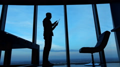 Silhouette of man using tablet computer standing by window at home Stock Footage