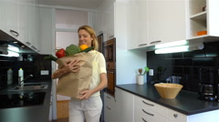Happy woman brings a large bag with groceries to the kitchen. Slow motion. Stock Footage