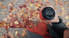 Autumn. Top view of young stylish woman holding a paper cup of coffee under the Stock Footage