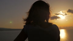 Contemplative woman back observing the sea during the sunset Stock Footage