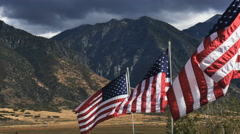 Close up-Sunlit American flags against dark sky and mountain Stock Footage