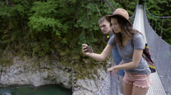 Hikers Stop On A Suspension Bridge To Take Photos With Smart Phone Stock Footage