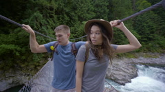 Nervous Couple Hold Onto Bridge As They Cross, High Above Whitewater Rapids Stock Footage