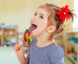 Girl licks candy on a stick Stock Photos