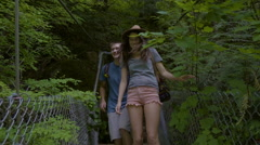 Adventurous Happy Couple Cross Bridge Together, Laugh, Push Branches Out Of Way Stock Footage