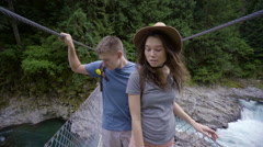 Closeup Of Hikers Crossing Suspension Bridge High Above White Water Rapids Below Stock Footage