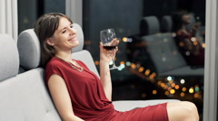 Happy woman drinking red wine while relaxing on sofa at home at night Stock Footage