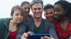 4k Happy mixed ethnicity group of friends pose for photo at the beach Stock Footage