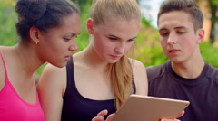Young friends reading bad news on tablet. Closeup of young people shocked Stock Footage