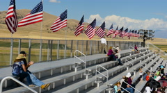 American flags fly over outdoor arena with spectators Stock Footage