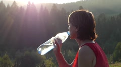 Silhouette of Woman That Drinking Water in the Mountains at Sunset. Stock Footage