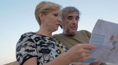 Tourist couple consulting a map to figure out where to go Stock Footage