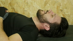 Fatigued athlete takes a breath lying on the ground Stock Footage