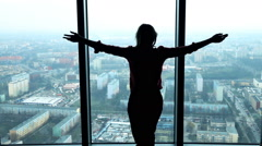 Silhouette of woman stretching arms and admire view form window, slow motion Stock Footage
