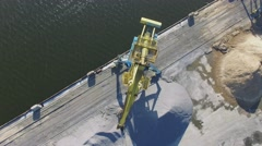 Several cranes on shore near piles of sand in South River Port Stock Footage