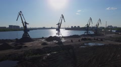 Cranes on shore near sand piles in South River Port at sunny day Stock Footage