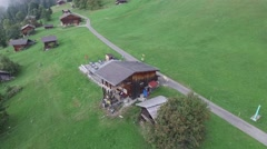 AERIAL FLY OVER SWISS MOUNTAIN VILLAGE AND THROUGH CLOUDS Stock Footage