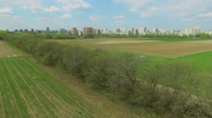 Cityscape and experimental grass fields at spring sunny day Stock Footage