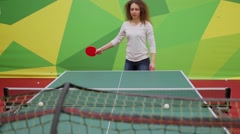 Woman learns to play ping-pong on table with large net in sport club Stock Footage