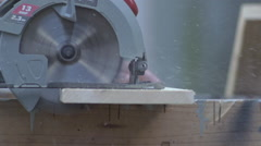 Slow Motion Circular saw cuts through board - side angle Stock Footage