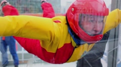Woman in helmet flies in air-tube with glass walls Stock Footage