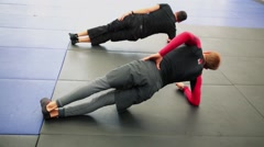 Coach and disciple make static exercise on floor in sport club Stock Footage