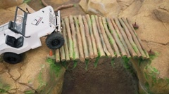 White toy truck overcomes wooden bridge above ravine Stock Footage