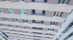 Tall dwelling house facade with balconies at sunny day. Aerial view Stock Footage