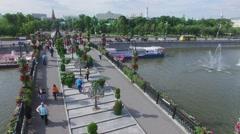 People walk on Tretyakov pedestrian bridge adorned by flowers Stock Footage
